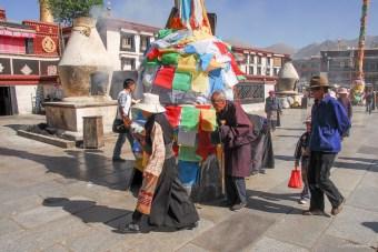 Drapeaux de prière et pélerins devant le Monastère du Jokhang - Lhassa - Tibet