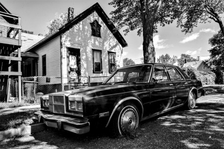 Altes unbenützte und verrottete chrysler Limousine steht vor einem verlassenen Haus. Detroit, USA September 2015 // Old rotted chrysler limousine which was not used for a long period of time is parking in front of a left and destroyed building in Detroit. Detroit, USA. September 2015