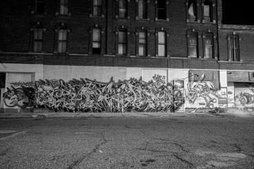 Obdachlose Person schläft am Boden vor einem mit Graffiti besprühter Lagerhalle in Detroit, USA September 2015 // Homeless person sleeps in front of a warehouse which has a big graffiti on it. Detroit, USA. September 2015