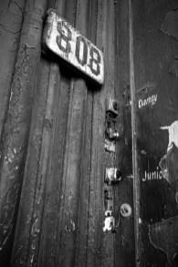 Hausnummernschild mit mit mehreren Klingeln eines historischen, kolonialen Gebäudes in Kuba, Havanna. November 2015 // Sign with a house number and bells of a historical, colonial building in Havanna, Cuba. November 2015