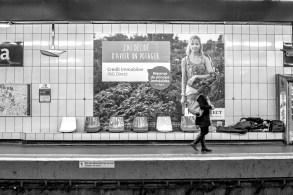 Ein obdachloser Mann schläft mit einem Schlafsack in einer Ubahnstation in Paris. Über ihm ist ein Werbeplakat der ING Bank angebracht, dass für Immobilienkredite wirbt. Paris, Frankreich. Dezember 2016 // Homeless guy is sleeping in the subway station with a sleeping bag. Advertising poster for real estate credit of the ING bank is next to him. Paris, France. December 2016.