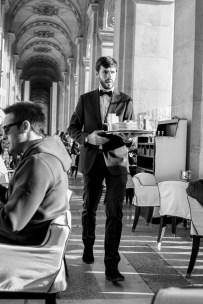 Kellner eines gut besuchten Restaurant Cafe nähe des Louvre Museums in Paris, Frankreich. Dezember 2016 // Waiter in a crowded restaurant close to the Louvre museum in Paris, France. December 2016.