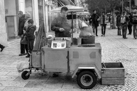 Straßenverkäufer verkauft Maroni die auf einem mobilen Verkaufsstand zubereitet werden in Lissabon, Portugal. Februar 2017 // Street vendor is selling chestnuts in streets of Lisbon, Portugal. February 2017