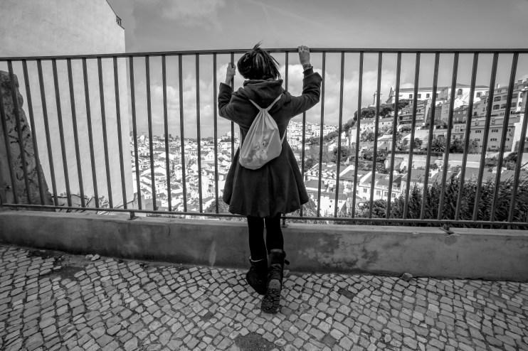 Touristin genießt den Ausblick von einer Anhöhe aus vor Gitterstäben auf Lissabon, Portugal. Februar 2017 // Tourist enjoys the view from a hill on Lisbon, Portugal. February 2017
