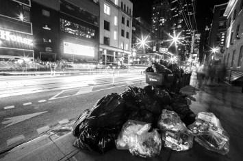 Große Ansammlung von Müll und Müllsäcken in Down Town Toronto, während im Hintergrund sich eine große Warteschlange vor einem Nachtclub bildet. Toronto, Kanada. Mai 2015 // Mountain of garbage in down town Toronto, while people are lining up in front of a night club. Toronto, Canada. May 2015