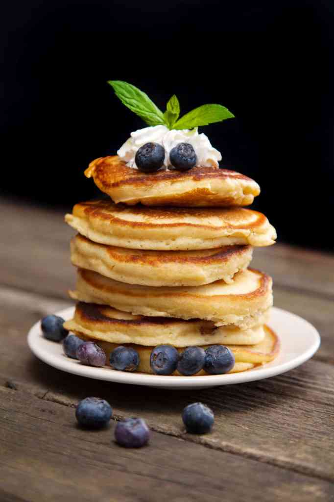 Delicious pancakes with blueberry, whipped cream and mint