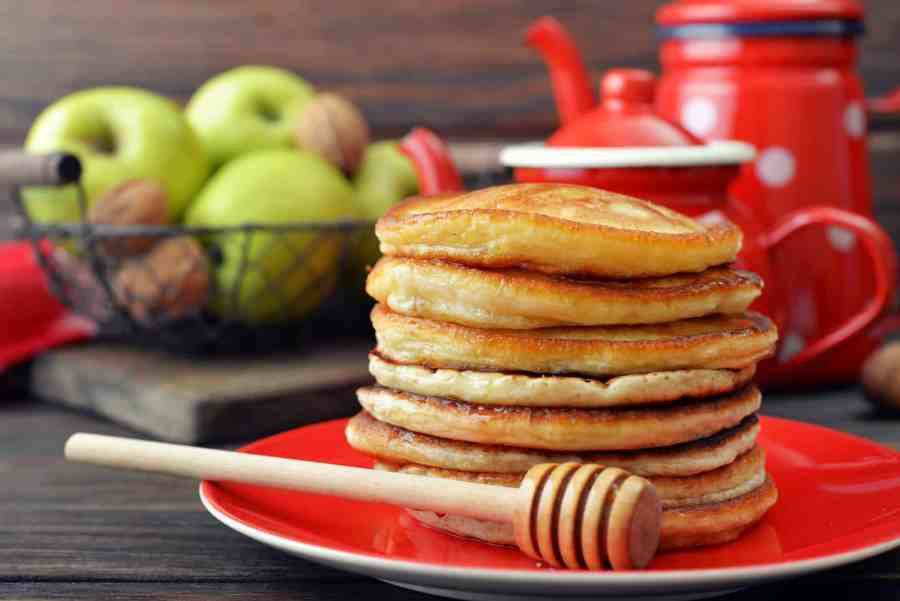 Stack of pancakes on plate with vintage teapots and fresh apples on wooden background