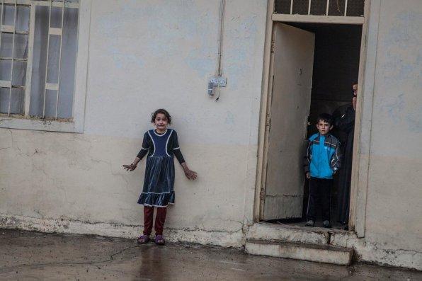 Frère et soeurs regardant les forces irakiennes traverser la cour de leurs maisons © Laurent Van der Stockt pour/for Le Monde / Getty