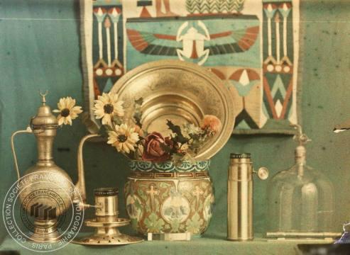 [Nature morte, bouquet de fleurs, vases et flacons], Anonyme, après 1907. - 1 photographie positive transparente: verre autochrome, couleur; 9,5 x 12 cm
