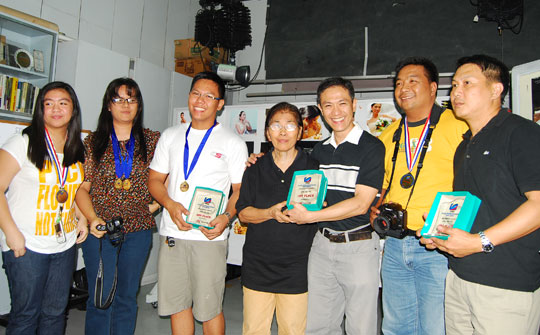 The overall winners of the Advanced Photography Workshop April-May 2009 pose with Prof. Cecilia S. Angeles during their graduation. From left to right: Chini Reyes 4th Place, Catherine Yason who won both Still Life and Low Key, John Tan 2nd Place, Prof. Angeles, Alex Zafra 1st Place, Michael Loyola 5th Place and Willi Cheng 3rd Place.