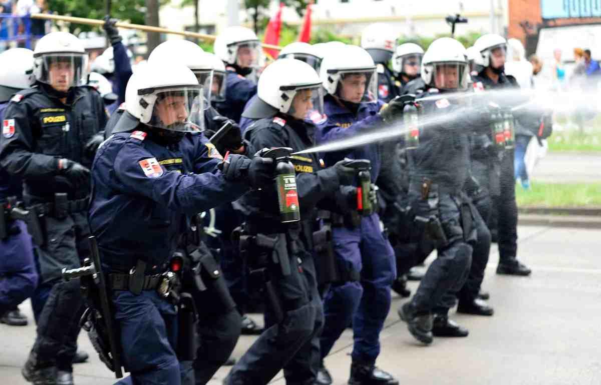 Einsatzeinheiten der Wiener Polizei spritzen die Demoroute mit Pfefferspray frei. Bild: Daniel Weber