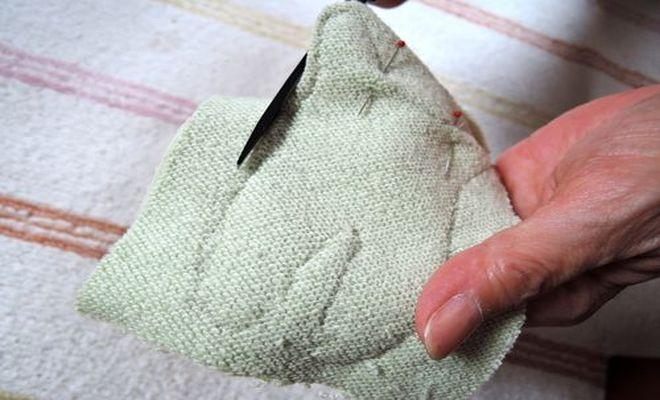 体・顔の部分の縫った糸にそって、布を切っていきます。