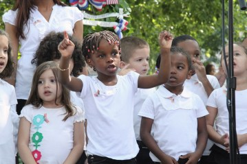 """Children from the Child Care Center sings a heart warming, """"You're Not Alone,"""" at the 9/11 memorial service."""