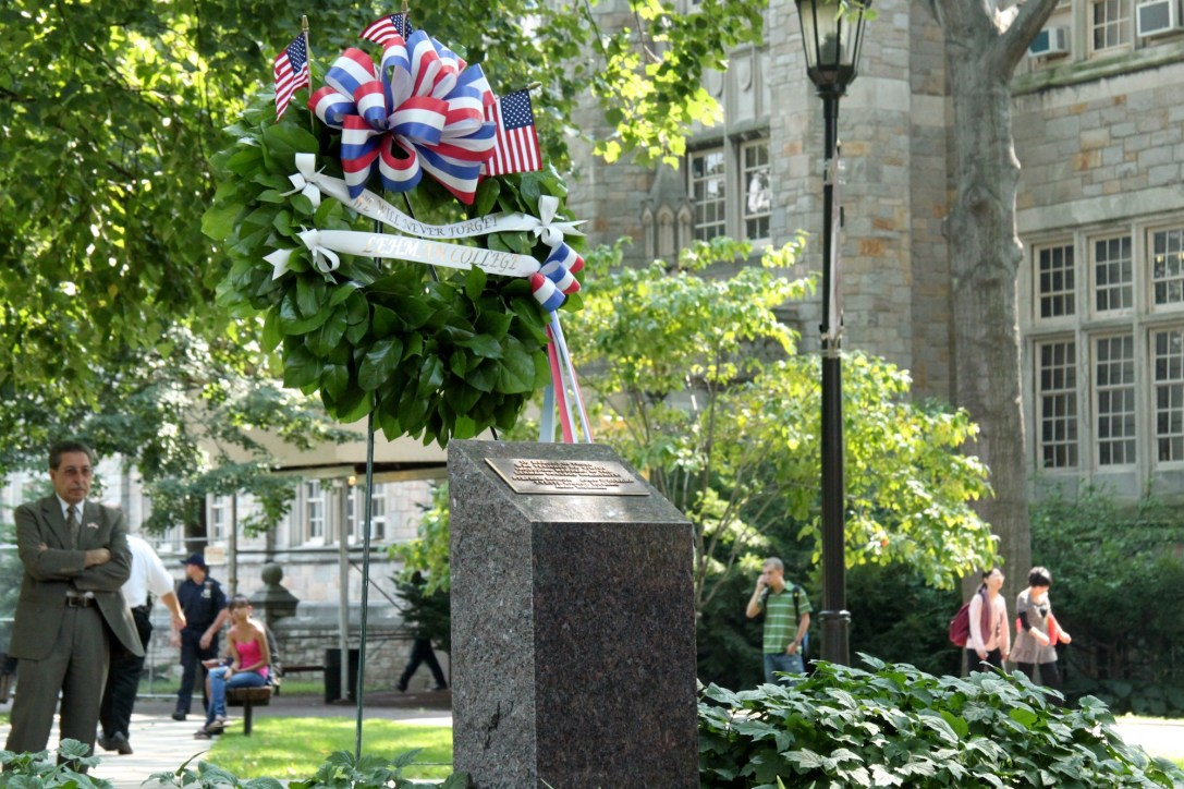 """A wreath with a ribbon that reads, """"We Will Never Forget,"""" stands next to the plaque dedicated to those who perished on 9/11/2001."""