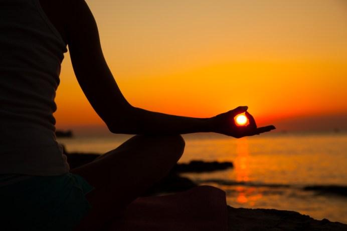 Posizione di meditazione dello yoga con un sole sullo sfondo