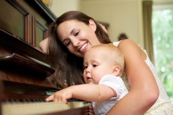 Una mamma che suona il pianoforte con il suo bambino piccolo