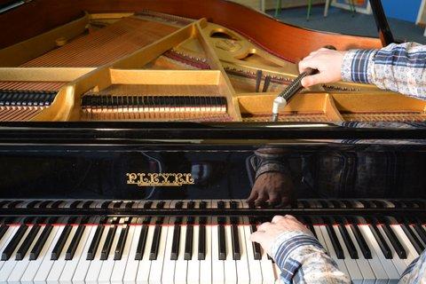 Pianostemmer Erik Kammenga stemt een piano, een vleugel