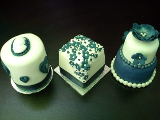 Mini cakes, covered and decorated with sugarpaste and flower paste decorations