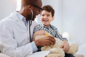 Enthusiastic male doctor sitting with boy while listening to plush bear through stethoscope and talking