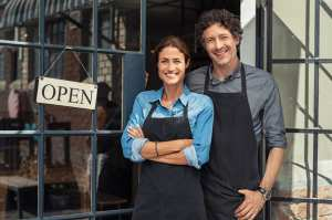 Two cheerful small business owners smiling and looking at camera while standing at entrance door. Happy mature man and mid woman at entrance of newly opened restaurant with open sign board. Smiling couple welcoming customers to small business shop.