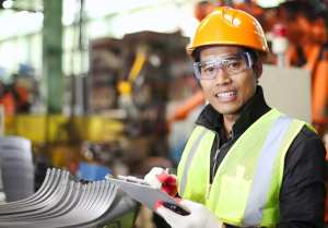 Portrait of young engineer wearing a hard hat and a high visibility jacket, taking notes on a notepad