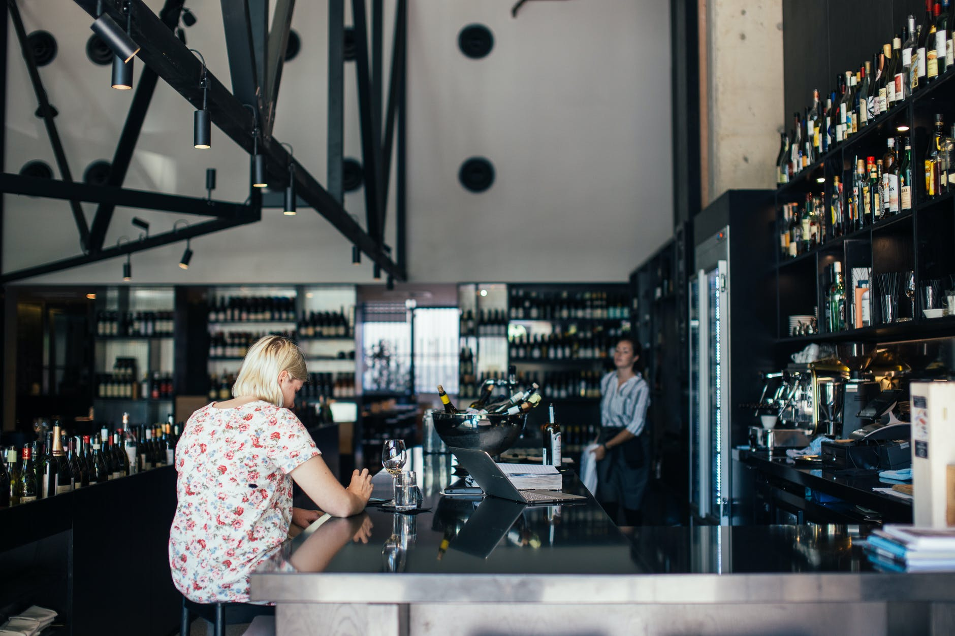woman sitting at bar counter in restaurant