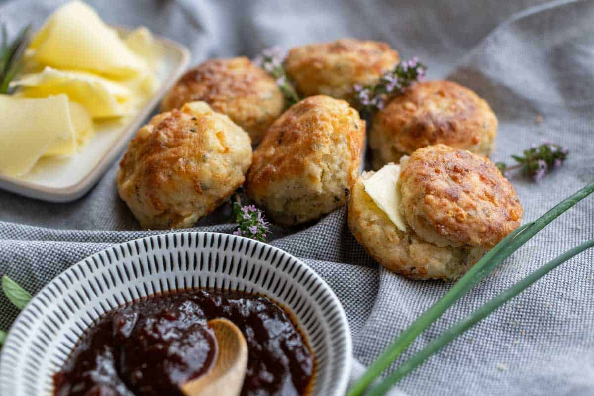 Savoury cheese scones with chutney and butter in dishes.