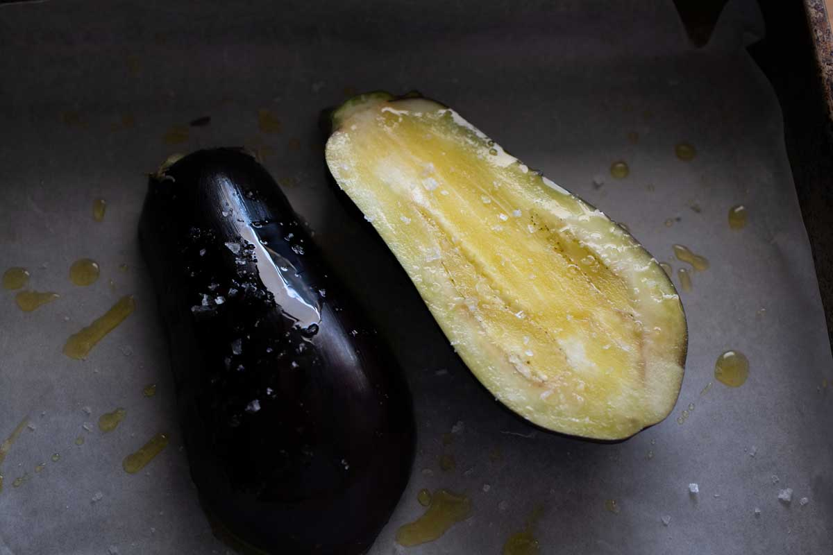 Whole eggplant cut in half showing inside and outside.
