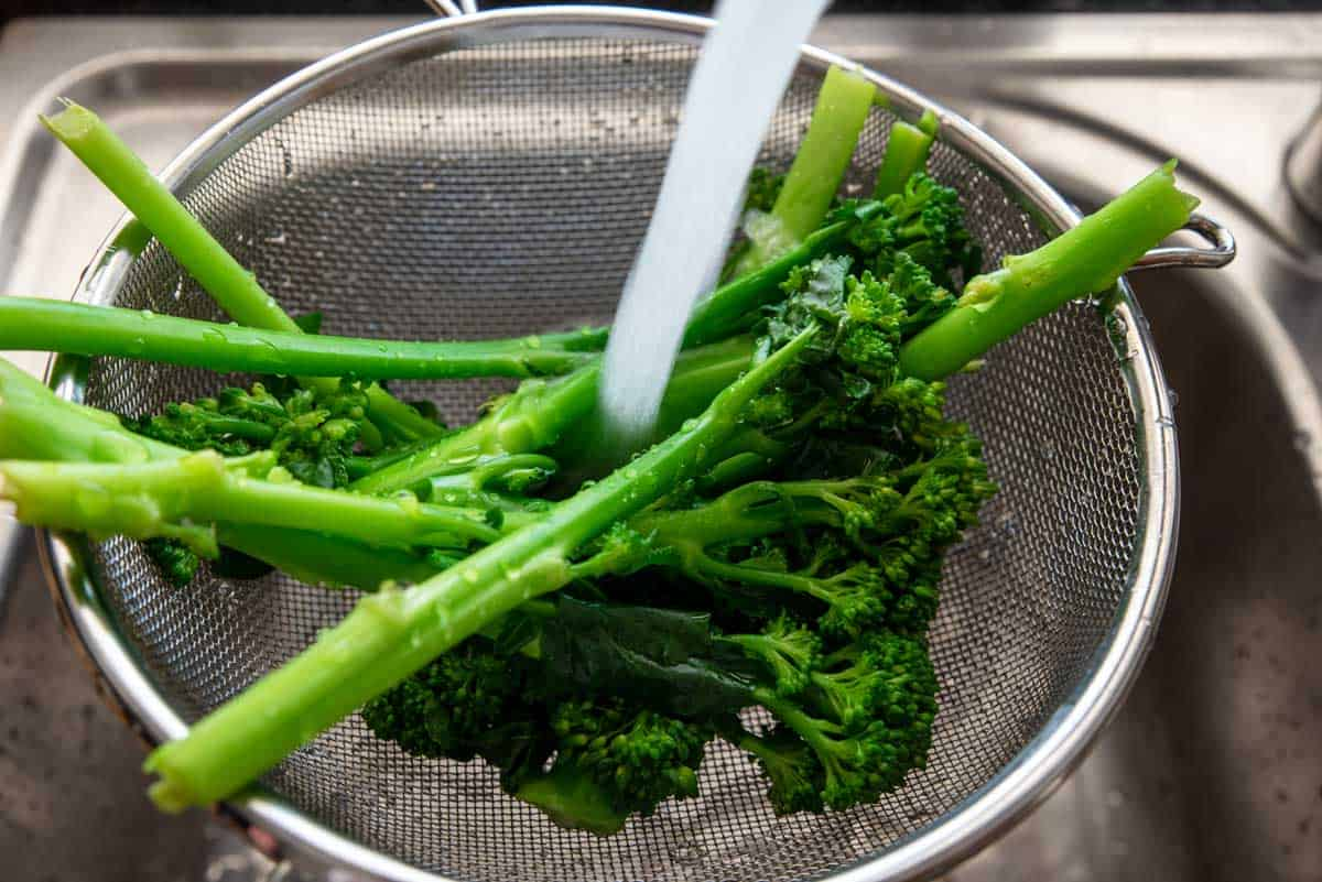 Florets of broccoli being rinsed under running water in a colander.