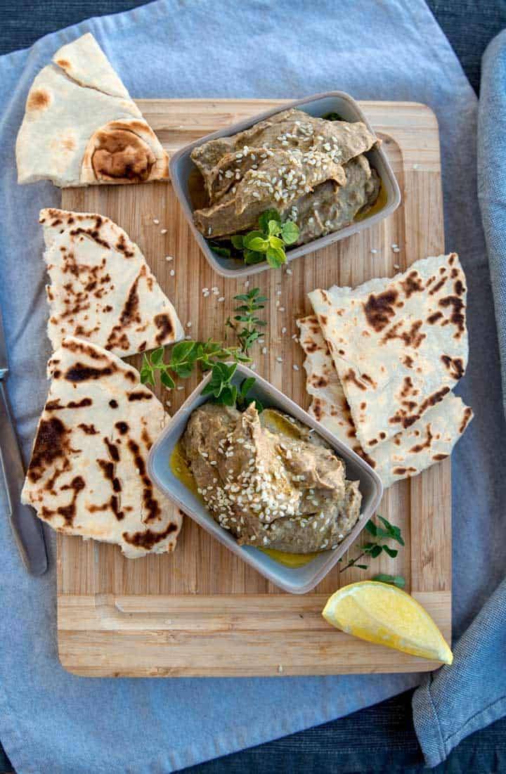 Babba ganoush eggplant dip with flat bread garnished with fresh herbs.