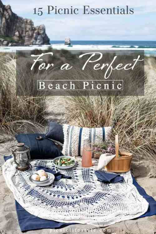 """Pinterest graphic of a picnic set up on the beach with text overlay - """"Beach picnic essentials"""""""
