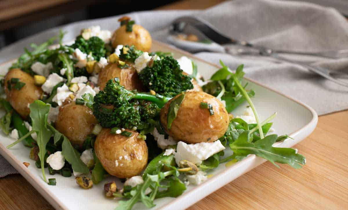 Plate of roast potato salad with broccolini and feta.