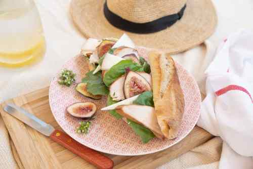 Fig and chicken baguette on a picnic blankets with straw hat.