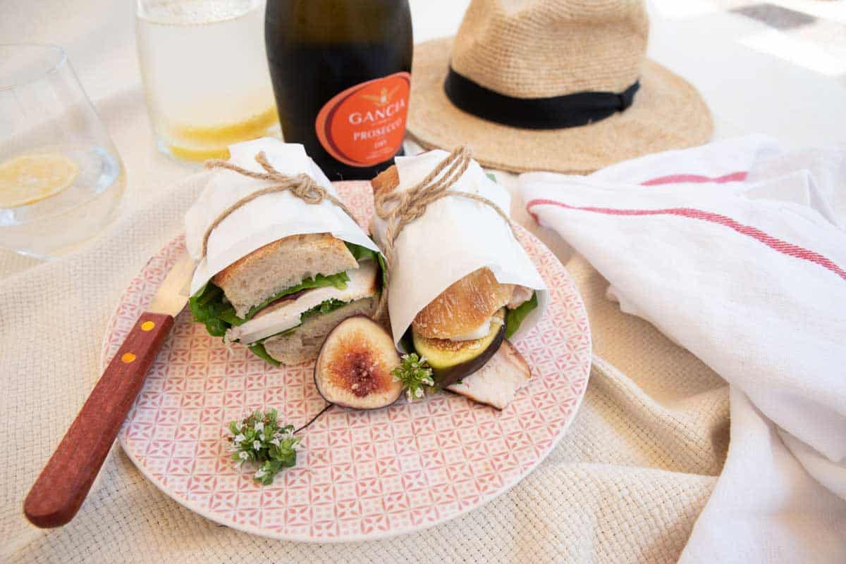 Chicken and fig baguette wrapped in paper tied with string at a picnic.
