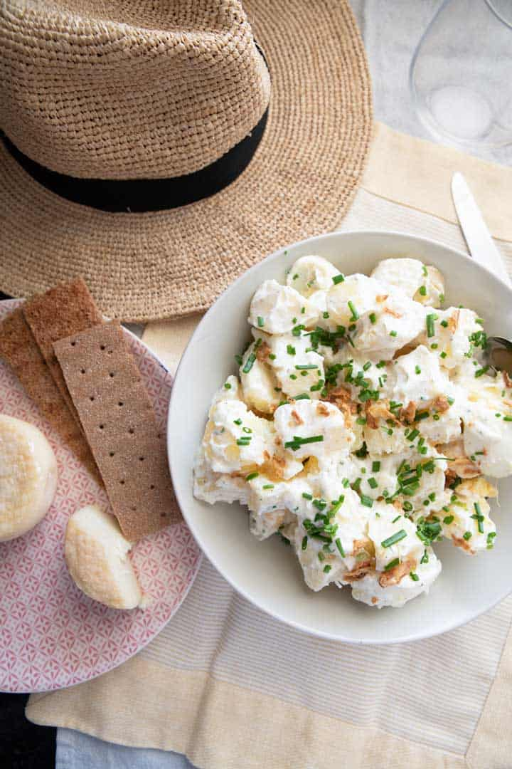 Potato salad next to summer straw hat.