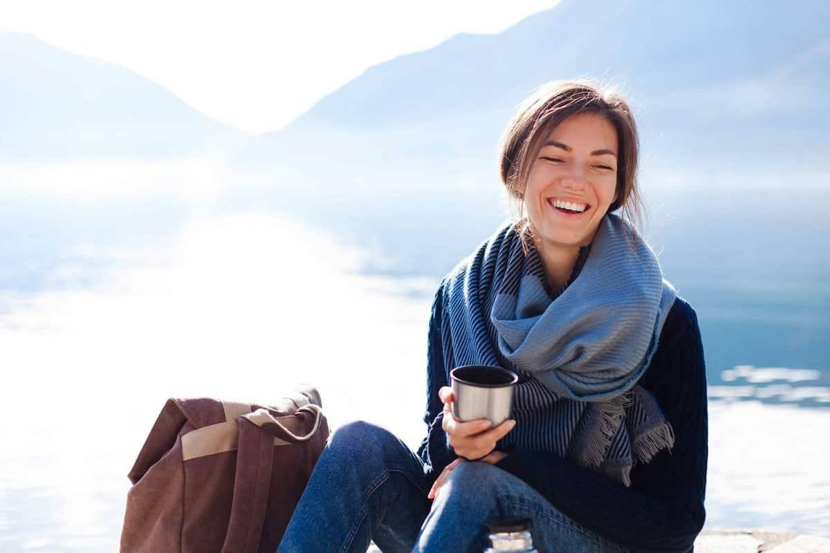 Smiling lady holding thermos cup in front of lake in winter.