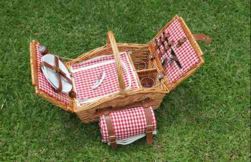 Picnic basket with red check lining on green grass