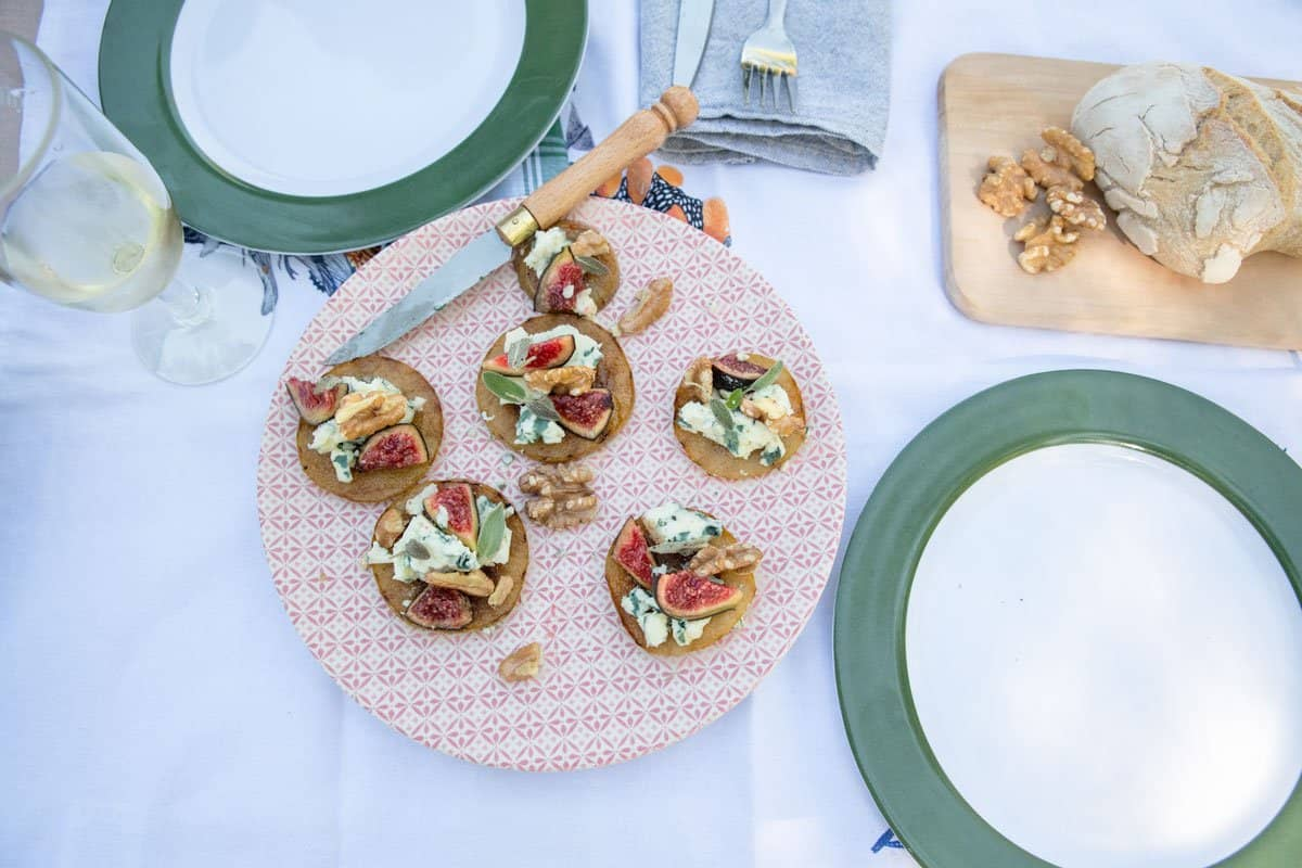 Grilled pear and blue cheese appetizers plated on a picnic blanket.