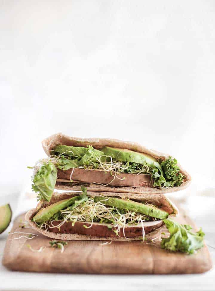 avocado and alfalfa pita cut in half and stacked.