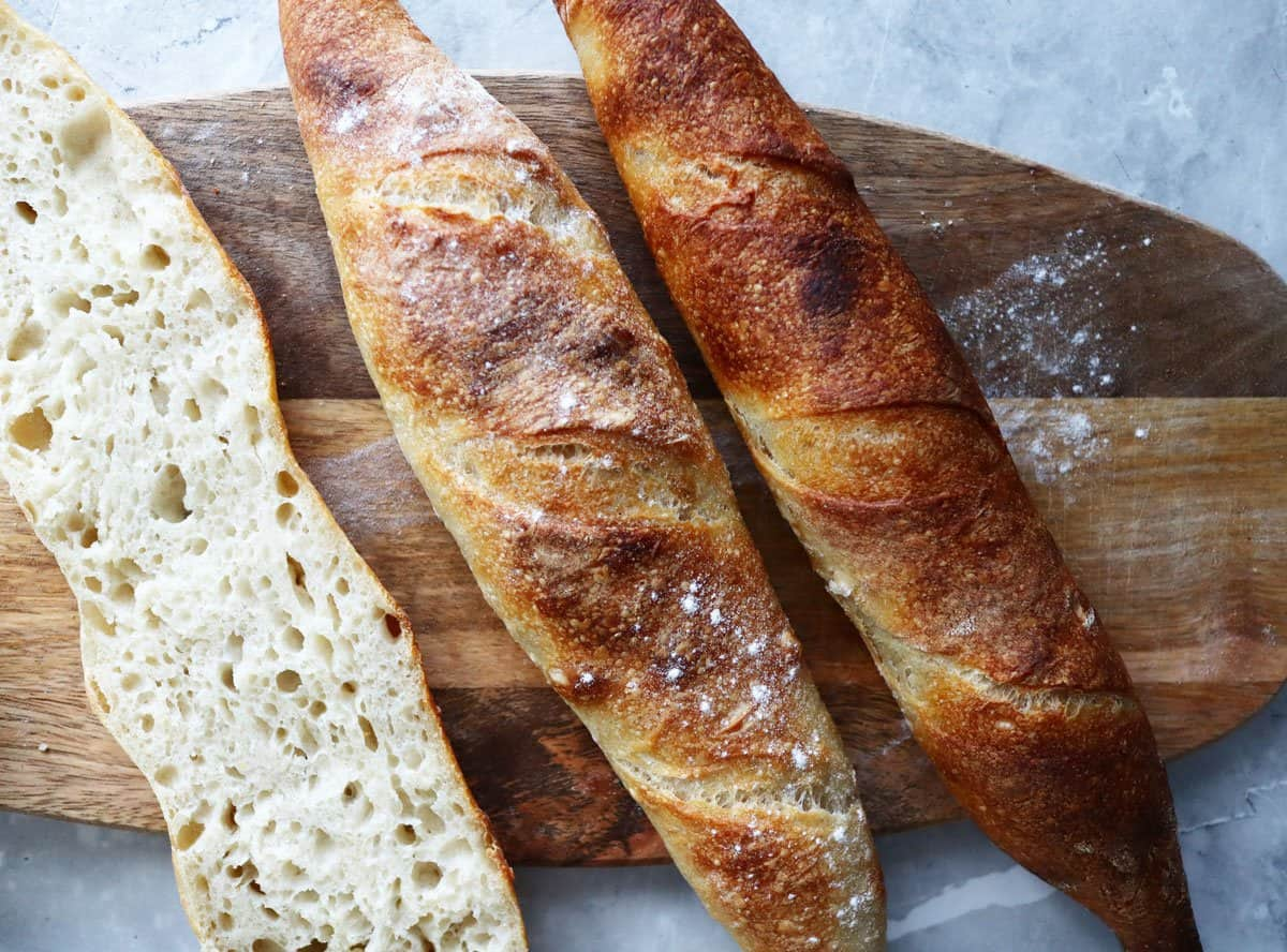 Sourdough baguettes on a bread board.