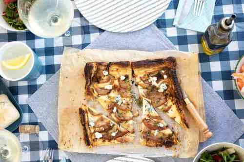 Slices of Pear and ricotta tart on baking paper laid on a blue check picnic table cloth.