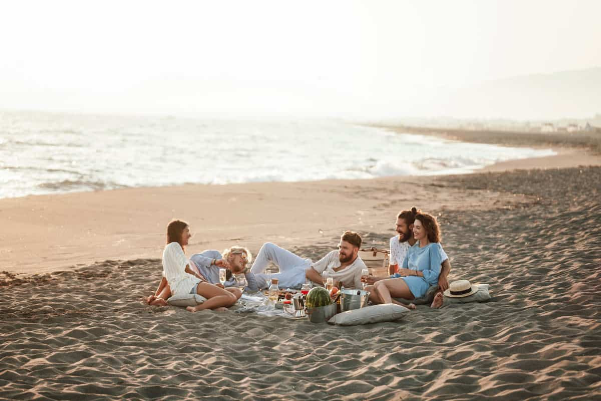 Group of friends enjoying a picnic on the beach at sunset.