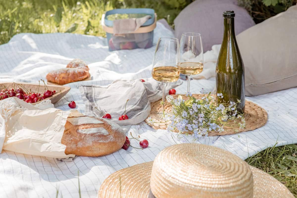 Picnic setting with spring flowers, bread, cherries and wine.