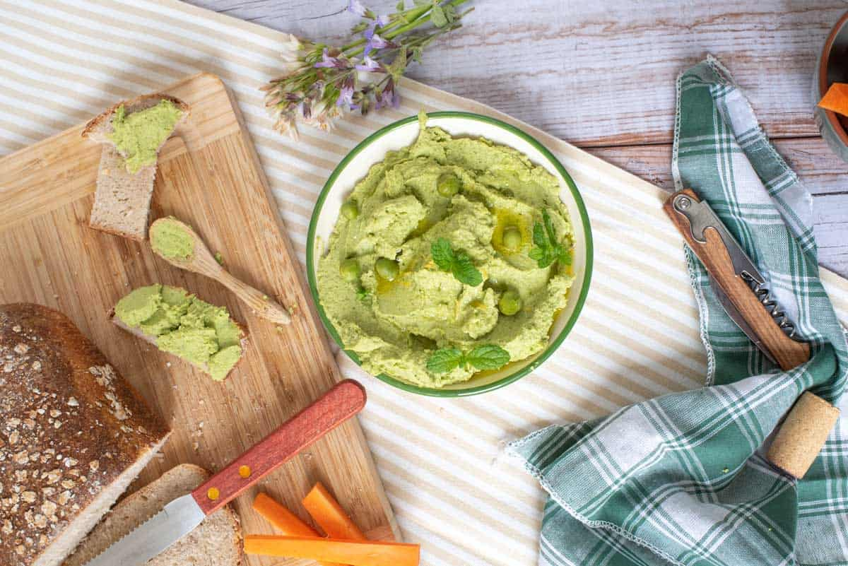 Minty pea dip on a picnic table with a wooden cutting board with bread and carrots sticks.
