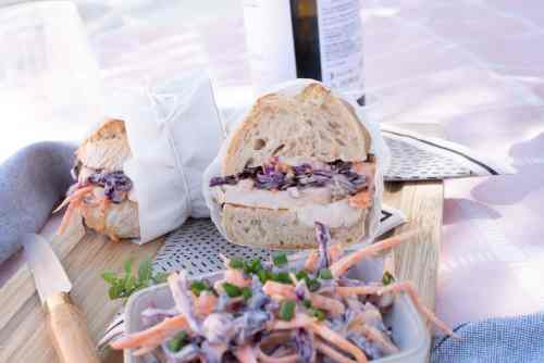 Chicken and coleslaw baguette cut in half wrapped in paper and tied with string.