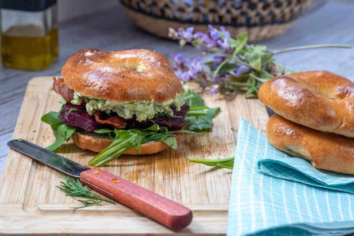 Bagel with beetroot and pea spread on a chopping board