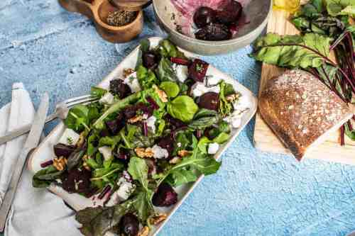Roasted beet salad on a square plate with bread loaf on a chopping board.