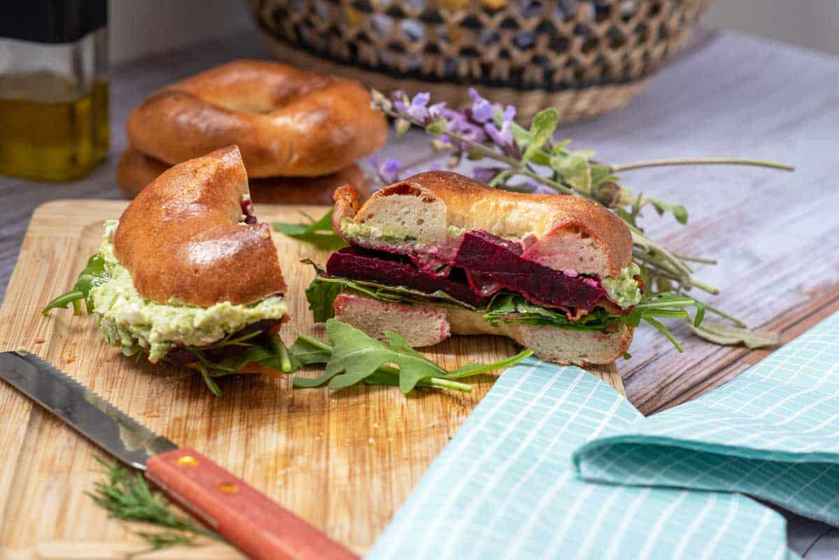 Bagel cut in half showing beet filling with green pea puree spread.