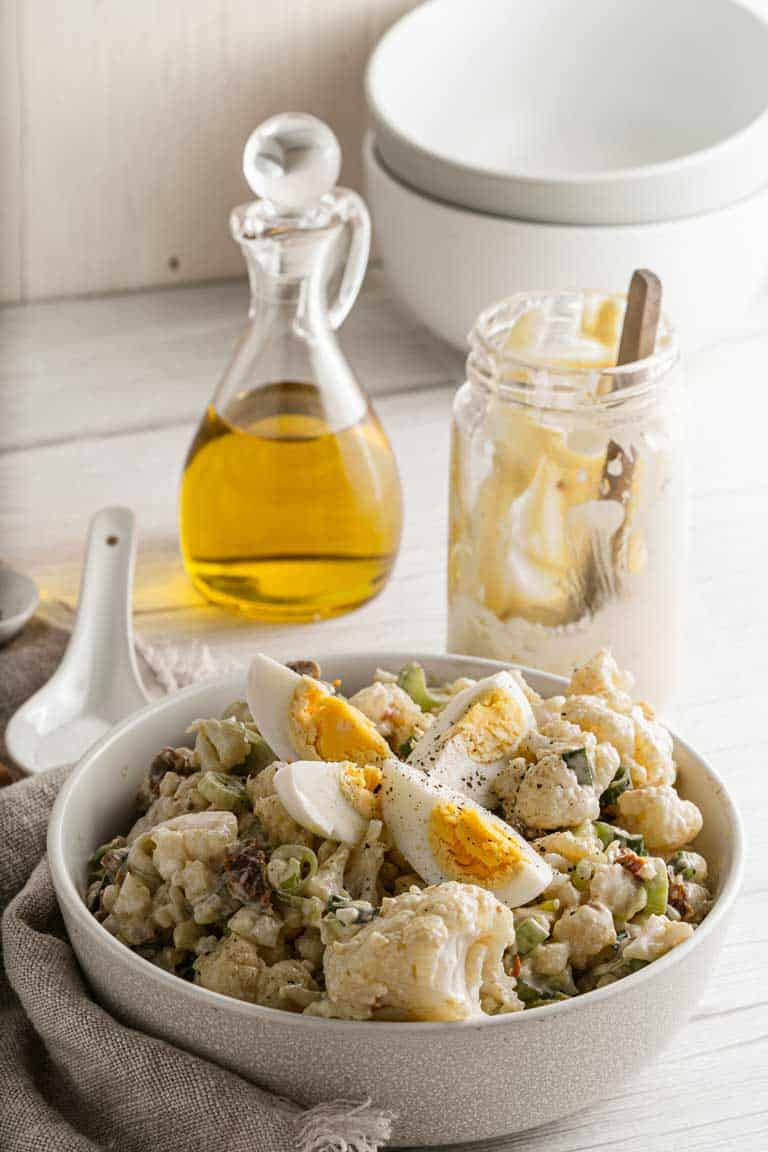 Bowl of cauliflower salad with eggs on top.