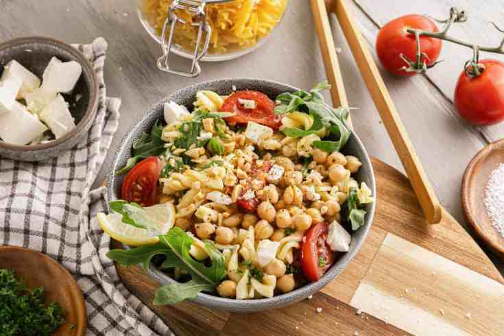 Chickpea Pasta Salad surrounded by fresh ingredients.